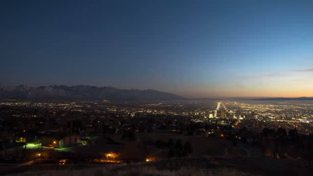 lockdown time lapse scenic view of illuminated city by mountains during sunset - salt lake city, utah - utah stock videos & royalty-free footage