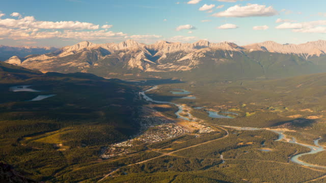 lockdown time lapse shot of city by river near mountains against sky on sunny day - jasper national park, canada - jasper national park stock videos & royalty-free footage