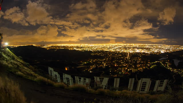 vidéos et rushes de lockdown time lapse shot of clouds moving above illuminated hollywood city at night - los angeles, california - enseigne hollywood