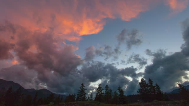 lockdown time lapse shot of cloudy sky over trees by vehicles at sunset - jasper national park, canada - jasper national park stock videos & royalty-free footage