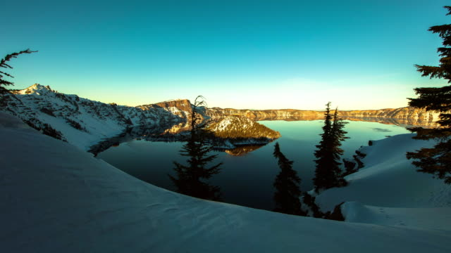 lockdown time lapse shot of crater lake amidst snowcapped mountains against sky - オレゴン州クレーター湖点の映像素材/bロール