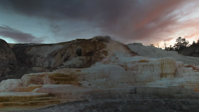 lockdown time lapse shot of famous mammoth hot springs against orange cloudy sky during sunset - yellowstone national park, wyoming - extinct stock videos & royalty-free footage