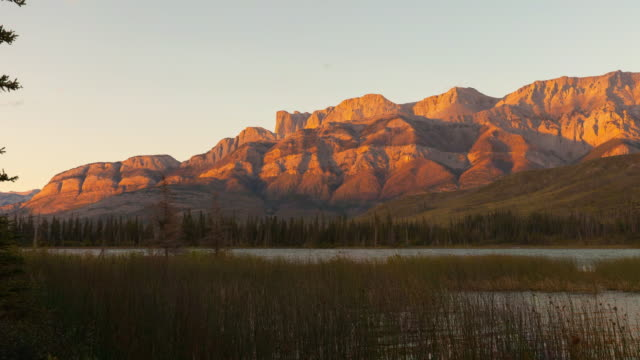 lockdown time lapse shot of grass in lake against rocky mountains against sky during sunset - jasper national park, canada - jasper national park stock videos & royalty-free footage