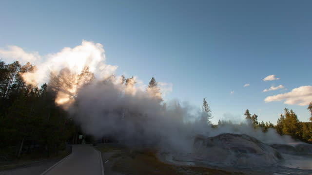 lockdown time lapse shot of grotto geyser emitting smoke by boardwalk against sky - yellowstone national park, wyoming - emitting stock videos & royalty-free footage