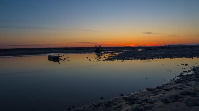 lockdown time lapse shot of idyllic view of river sunset against sky - delta junction, alaska - 男漁師点の映像素材/bロール