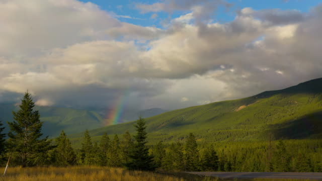 lockdown time lapse shot of rainbow over green mountains by vehicles on road against sky - jasper national park, canada - jasper national park stock videos & royalty-free footage