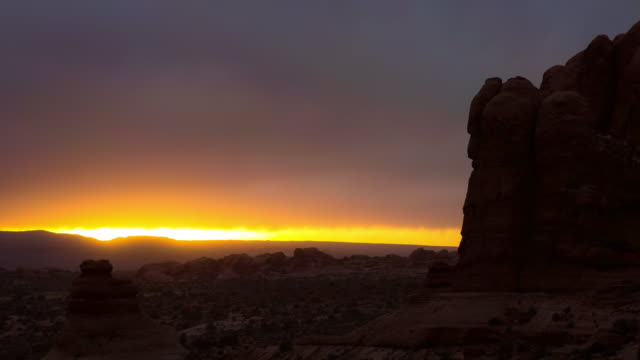 lockdown time lapse shot of rocky landscape against cloudy sky during sunset - arches national park, utah - 堆積岩点の映像素材/bロール