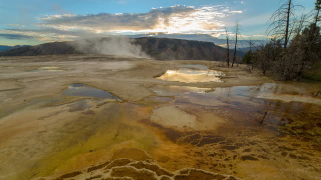 lockdown time lapse shot of smoke on hot spring against sky at sunrise - yellowstone national park, wyoming - sulphur stock videos & royalty-free footage