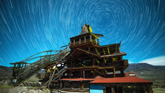 lockdown time lapse shot of star trails over famous the smith mansion at night - temple building stock videos & royalty-free footage