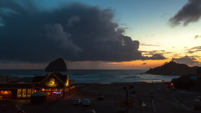 lockdown time lapse shot of storm clouds approaching towards vehicles by brewpub at beach during sunset - cannon beach, oregon - cannon beach stock videos & royalty-free footage
