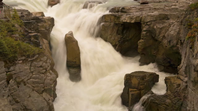 lockdown time lapse shot of tourists by waterfall through rocks at national park - jasper national park, canada - jasper national park stock videos & royalty-free footage