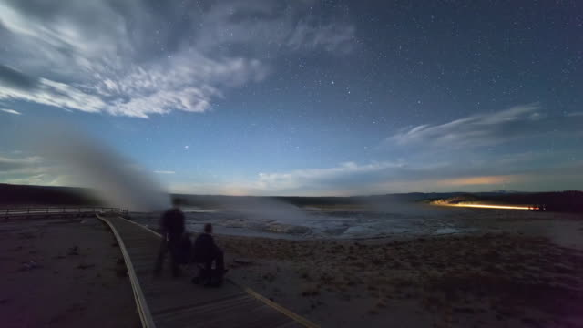 lockdown time lapse shot of tourists on boardwalk by geyser against sky at night - yellowstone national park, wyoming - fast motion stock videos & royalty-free footage