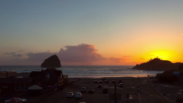 lockdown time lapse shot of vehicles by brewpub at beach against sky during sunset - cannon beach, oregon - cannon beach stock videos & royalty-free footage