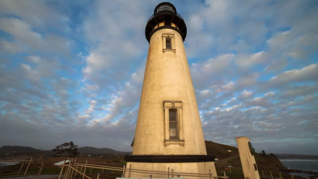 lockdown time lapse shot of yaquina head lighthouse against cloudy sky during sunset - newport, oregon - newport oregon stock videos & royalty-free footage