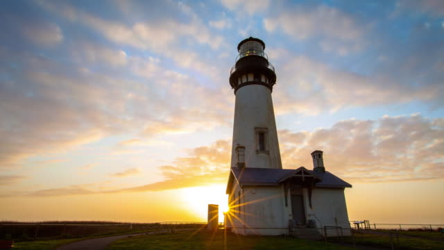 lockdown time lapse shot of yaquina head lighthouse against orange sky during sunset - newport, oregon - newport oregon stock videos & royalty-free footage