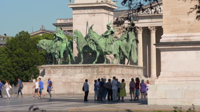 lockdown: tourists mill in front of massive bronze statues in heroes square - 偶蹄類点の映像素材/bロール