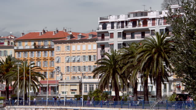 lockdown: tourists stroll in front of architecture on the promenade des anglais - ヤシ点の映像素材/bロール