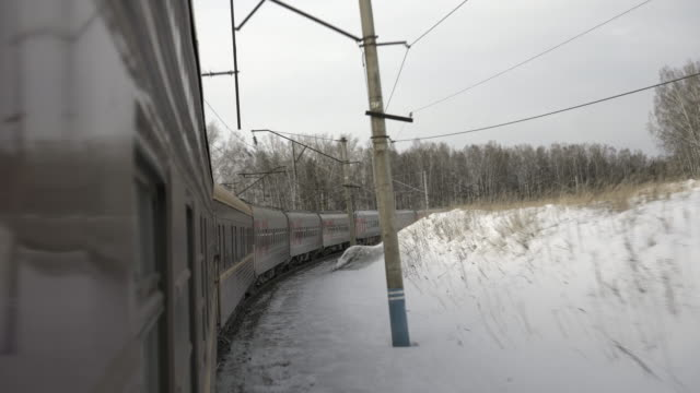 vídeos de stock, filmes e b-roll de lockdown: train passing through the tracks with the snow covering the surface of the area - trans-siberian railway, russia - russia