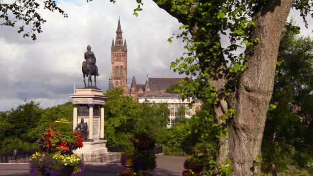 lockdown: tree before equestrian statue in lovely garden before towering sandstone cathedral in sunshine - glasgow, scotland - architectural column stock videos & royalty-free footage