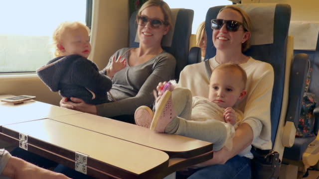 vidéos et rushes de lockdown: two toddlers sitting on moms on a train - stationary