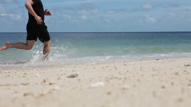 ws lockdown view of a beach and a man running past - fitzroy island stock videos and b-roll footage