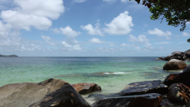 ws lockdown view of a beach with rocks on the shoreline - fitzroy island stock videos and b-roll footage