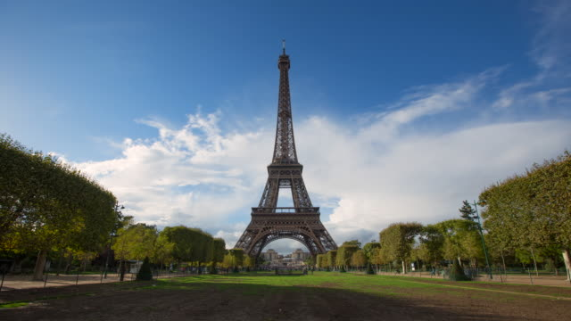 vidéos et rushes de lockdown wide time-lapse: the eiffel tower of paris standing high around the nature filled city - large