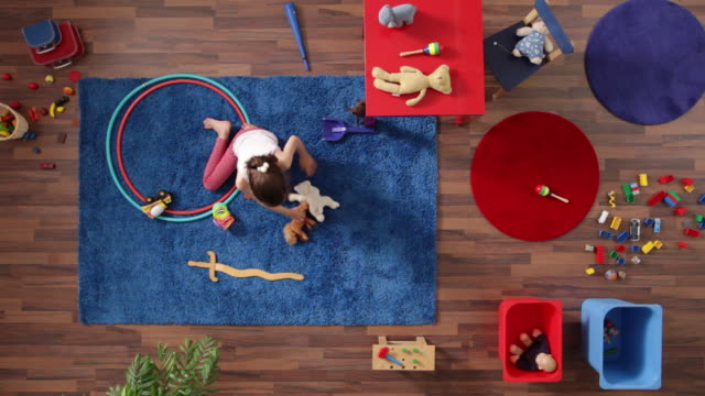 ms, lockdown, young girl playing in a room with a lot of toys, overhead view - ラグ点の映像素材/bロール