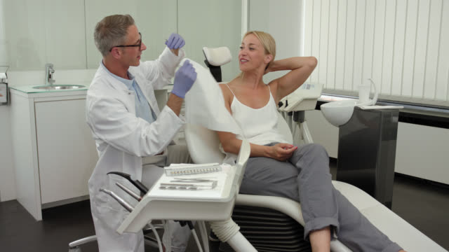 vídeos y material grabado en eventos de stock de dentist's office - mid adult dentist with short greying hair and glasses in white medical doctor's coat with female patient with long blonde hair on the chair, doctor taking off dental bib napkin serviette surrounded by equipment and good by hand shake. - camisa de polo