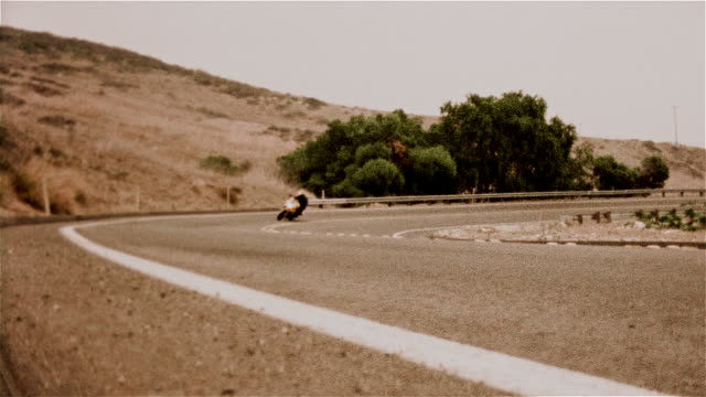 locked down shot of motorcyclist rounding bend / passing camera - biker jacket stock videos and b-roll footage