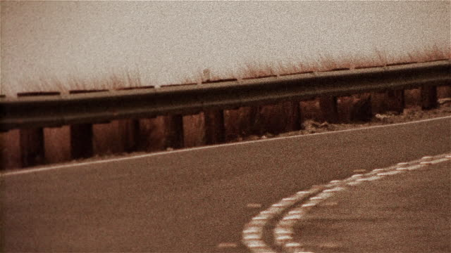 locked down shot of motorcyclist rounding bend - biker jacket stock videos and b-roll footage
