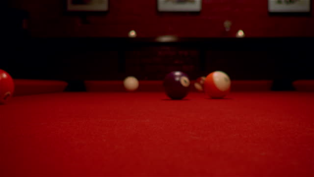 Locked down shot of pool balls scattering across red pool table after break
