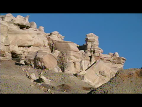 locked down wide shot of rock formations in sharp relief against clear blue sky in badlands of bisti/de-na-zin wilderness area / new mexico - レターボックス点の映像素材/bロール