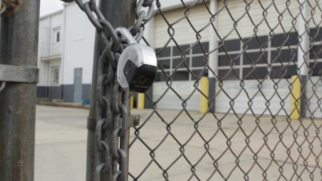 vídeos de stock e filmes b-roll de locked gate in front of closed factory on february 19 2012 in washington dc - montagem