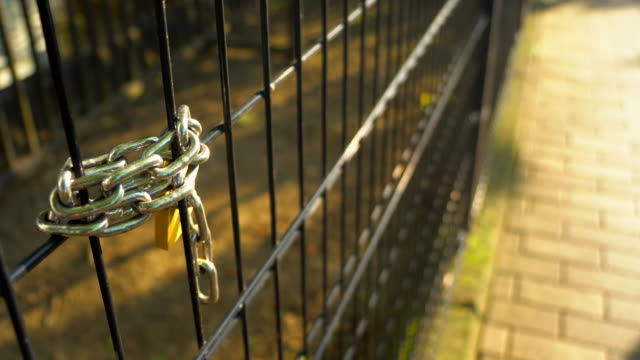 locked gate with iron chain and padlock - chain object stock videos & royalty-free footage