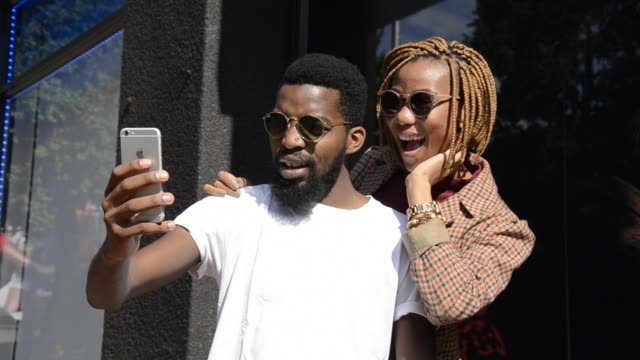 locked off ms of african ethnicity couple taking pictures using mobile phone/ johannesburg/ south africa - braided hair stock videos & royalty-free footage
