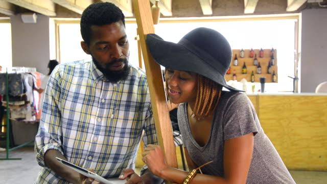 locked off ms of african ethnicity couple using digital tablet/ johannesburg/ south africa - タータンチェック点の映像素材/bロール