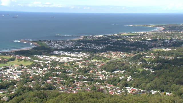 vídeos de stock e filmes b-roll de locked off high shot of wollongong taken from the northern part of the illawarra escarpment featuring port kembla breakwater lighthouse illawarra... - expansão urbana
