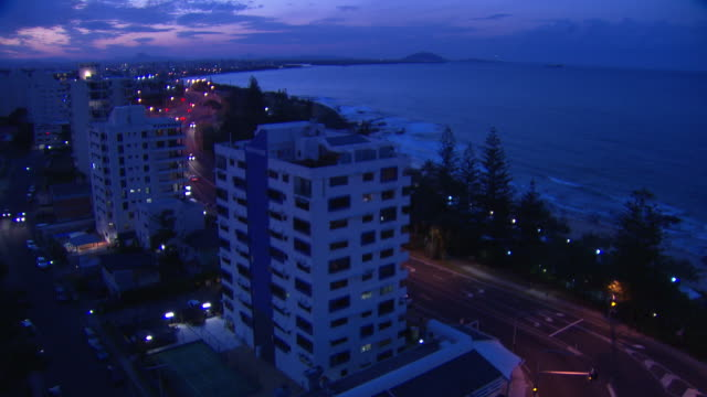 vidéos et rushes de locked off high wide shot at dusk / looking northwest over row of beachfront apartment blocks and foreshore coastline, towards the coral sea /... - phare de véhicule