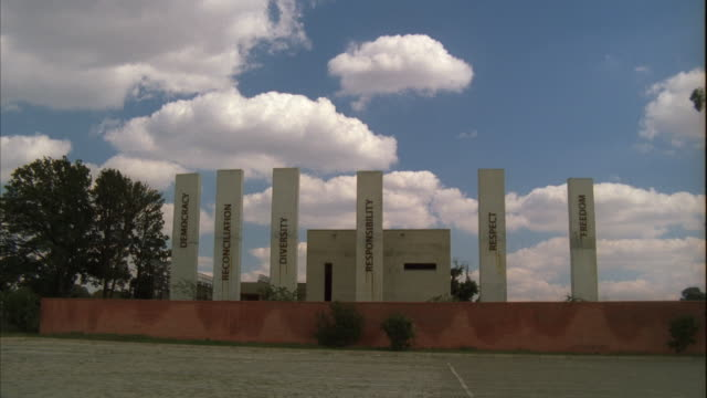 locked off long shot of concrete pillars with words on it at the apartheid museum - apartheid stock videos & royalty-free footage