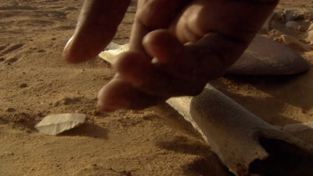 Locked off shot of a person picking up an elongated stone tool