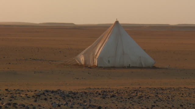 vidéos et rushes de locked off shot of a tent in the middle of a desert - tente