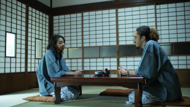 stockvideo's en b-roll-footage met vergrendeld schot van paar in afwachting van maaltijd aan tafel in ryokan - ryokan