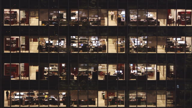 locked off tight shot of office block at dusk - ufficio video stock e b–roll