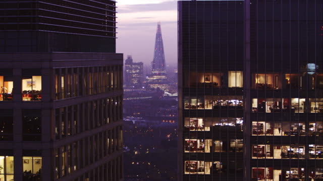 locked off wide shot of office block at dusk - office block exterior stock-videos und b-roll-filmmaterial