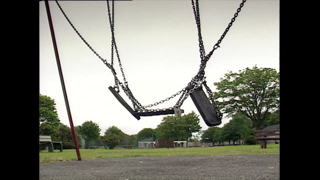 cu of locked swings in playground swaying in breeze; 1993 - 1993 stock videos & royalty-free footage
