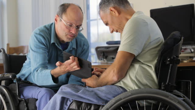 vídeos de stock e filmes b-roll de locked-on shot of man with friedreich's ataxia and limited dexterity showing tablet to his friend with spinal cord injury - cadeira de rodas