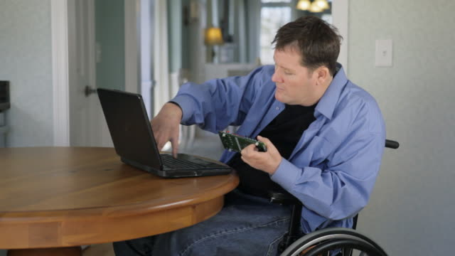 vídeos de stock e filmes b-roll de locked-on shot of man with spinal cord injury and quadriplegia reviewing circuit board design with laptop - paralisia