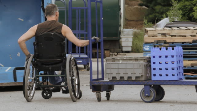 vídeos y material grabado en eventos de stock de locked-on shot of man with spinal cord injury in wheelchair moving freight with a hand truck in loading dock - silla de ruedas trabajo