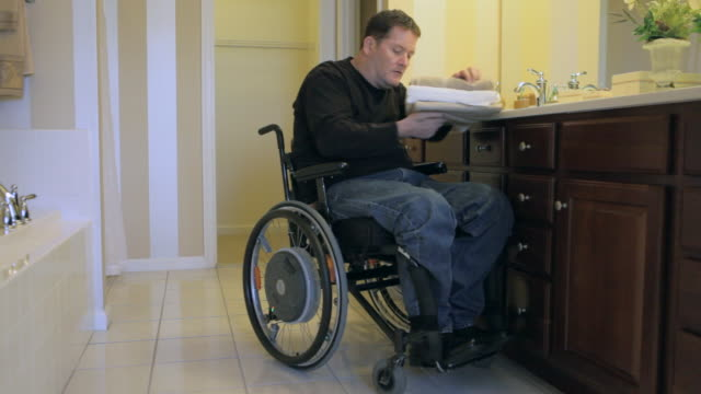 vídeos de stock e filmes b-roll de locked-on shot of man with spinal cord injury in wheelchair neatening his bathroom - paralisia